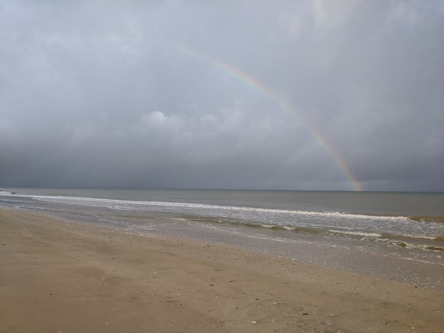 A rainbow over the ocean and beach at Utah Beach in Normandy