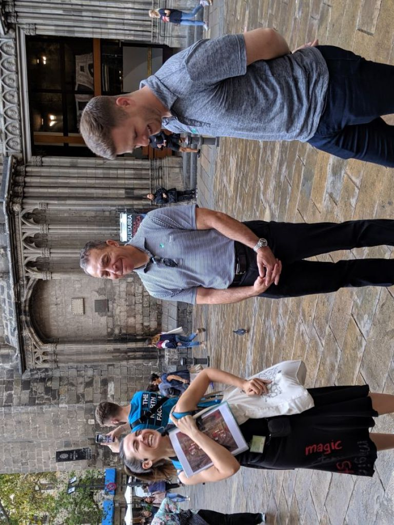 a tour guide and two guests in front of a cathedral in barcelona