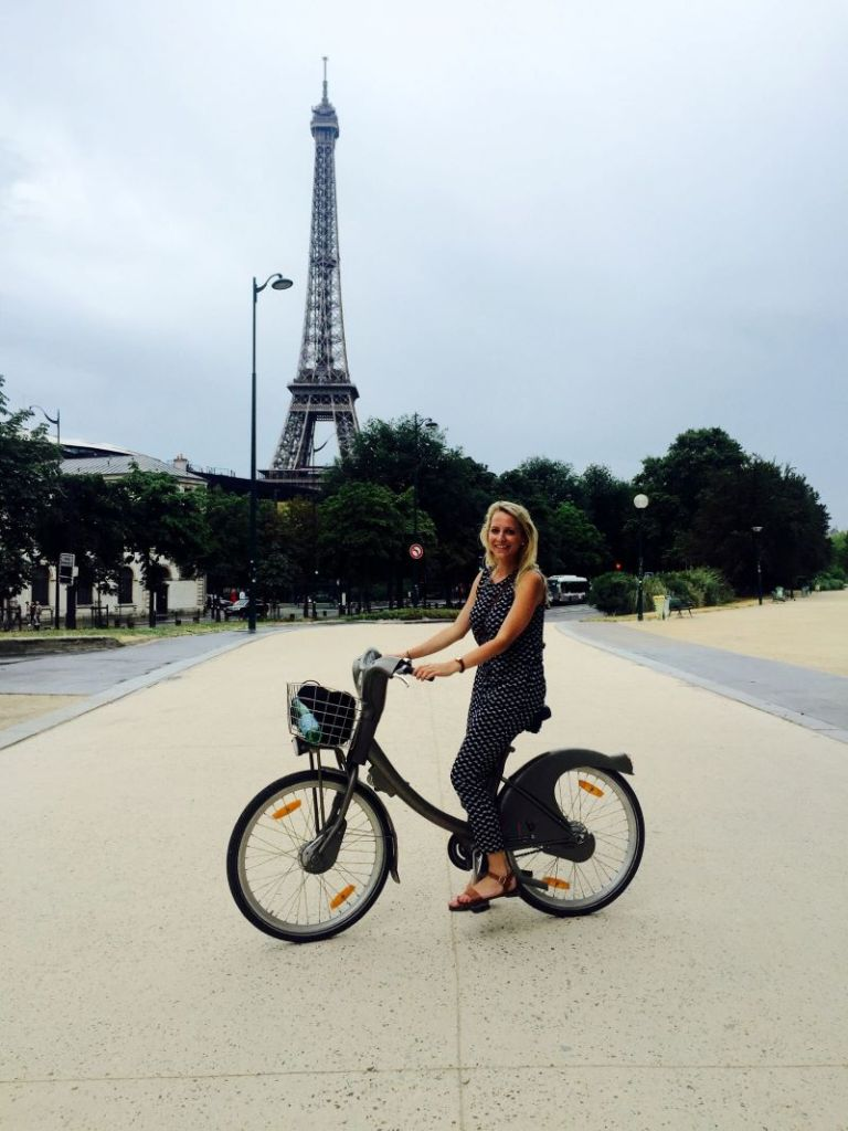 A blonde young woman on a bike in Paris with the Eiffel Tower in the background.