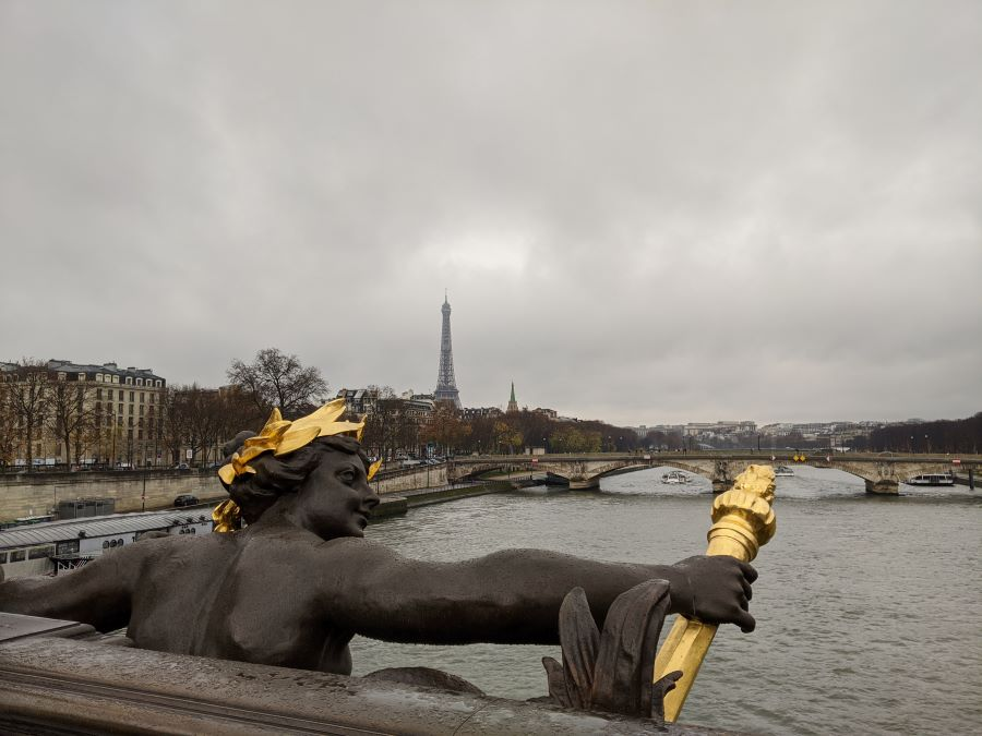 A statue on the Pont Alexander III bridge in Paris with the Eiffel Tower in the background.