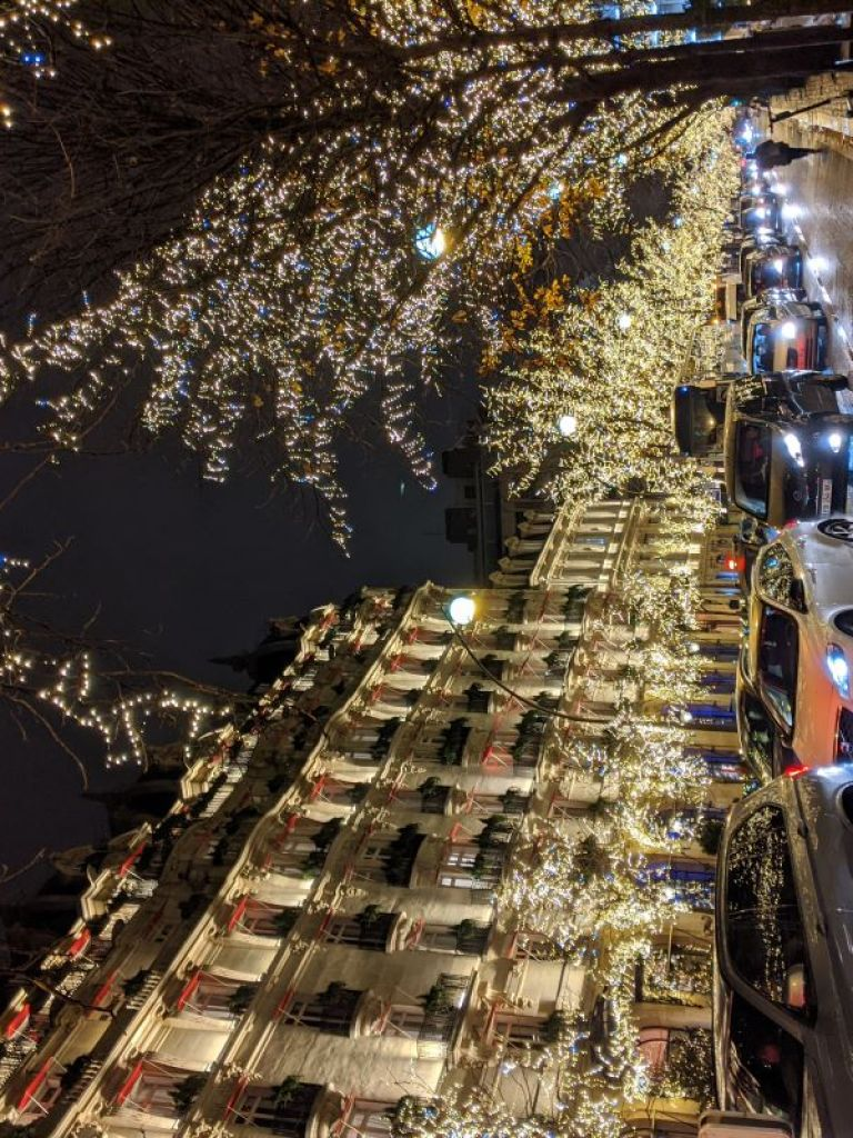 Traffic along a busy street in Paris. The trees and buildings along the street at lit with Christmas lights.