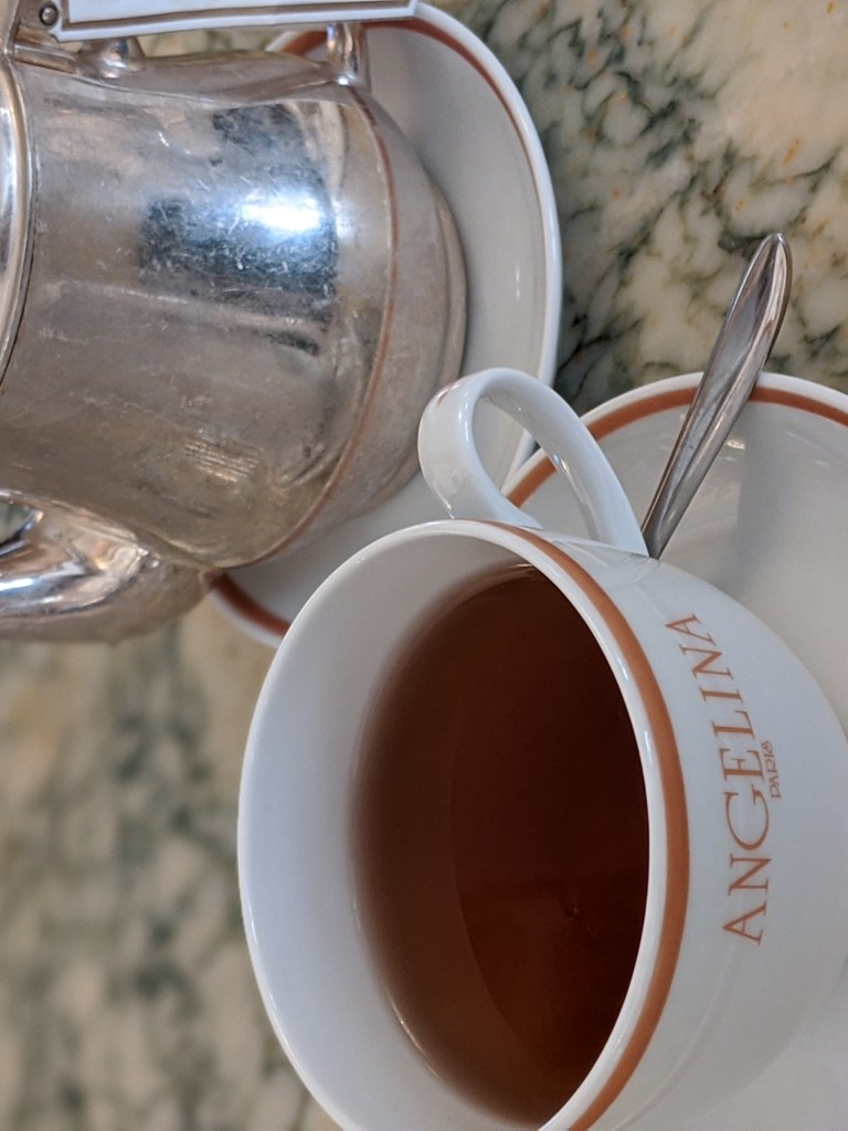 A cup of tea and a tea pot at Angelina Tea Room in Paris.