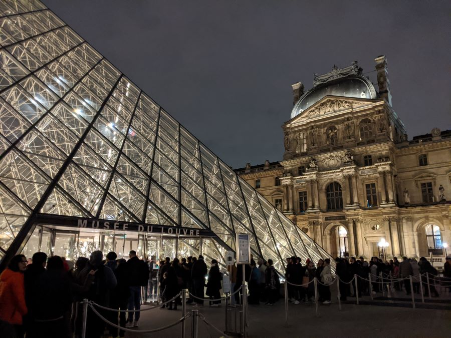 A long line outside of the Louvre pyramid in the evening.
