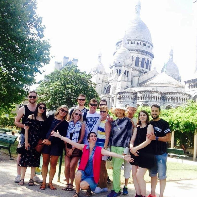 A group of 12 people posing for a photo on an organized walking tour in Paris.