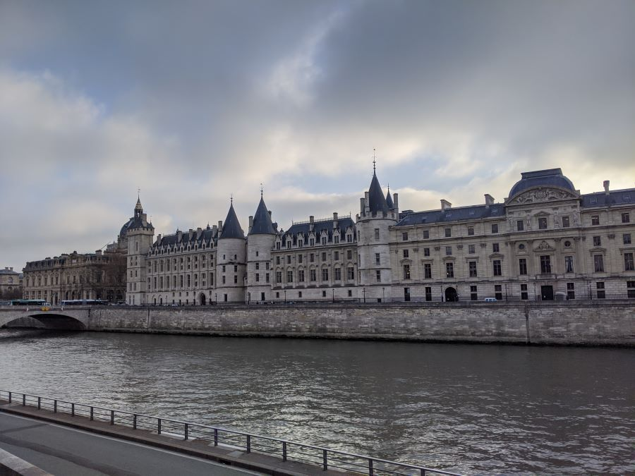 A long stone building along the Seine River with grey/blue spires.