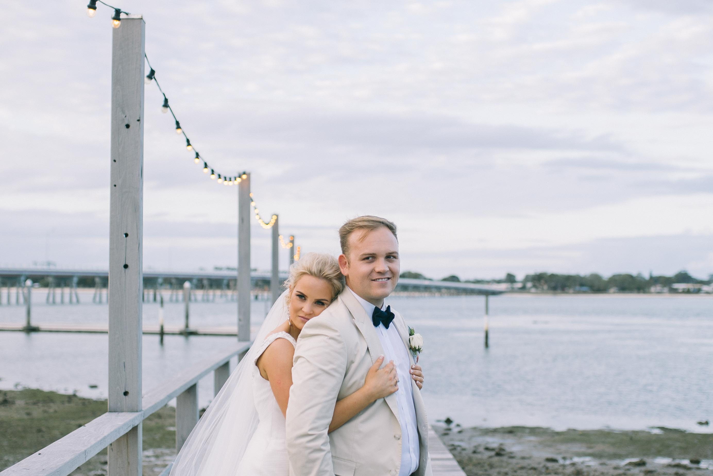 bride and groom in front of water