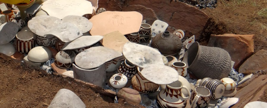 Anasazi trench kiln is loaded with replica pottery