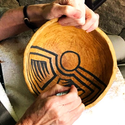 a pottery student paints her bowl