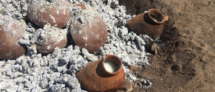 Two culinary shoe pots cooking parolee in hot coals