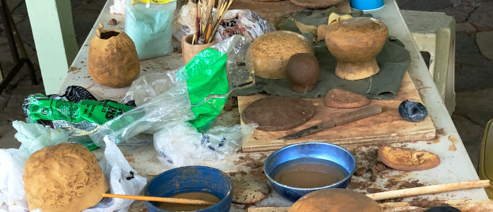 A work table with student's replica pots in various stages of production.