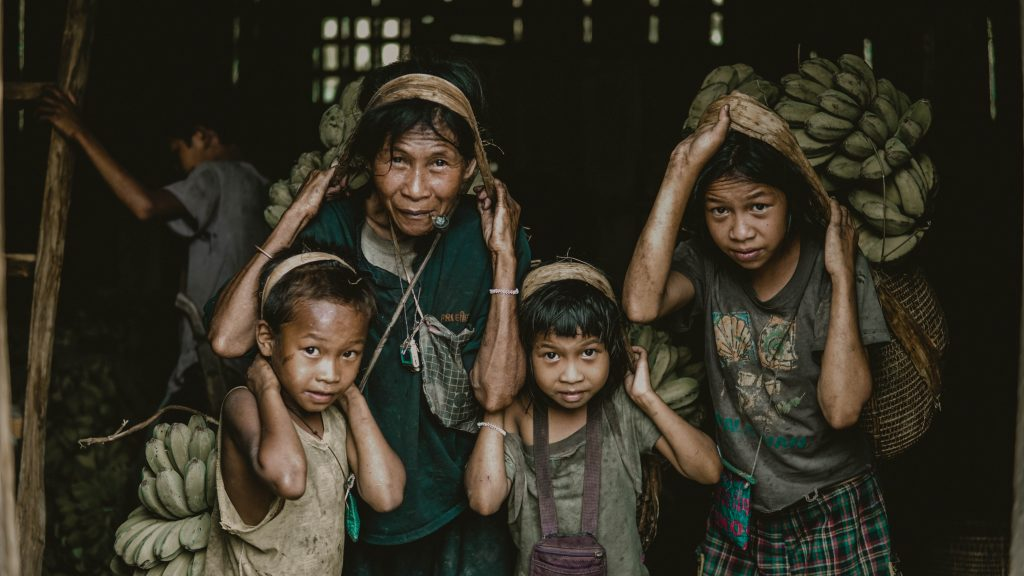 Poor family in the Philippines holding collected bananas from the mountains