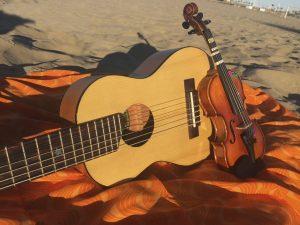 Guitalele y violín 1/16 sobre un pareo naranja en la arena de la playa