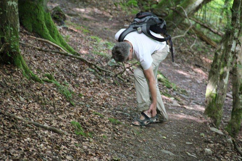 Ein Wanderer auf einem Pfad, er bückt sich nach seinen Wandersandalen