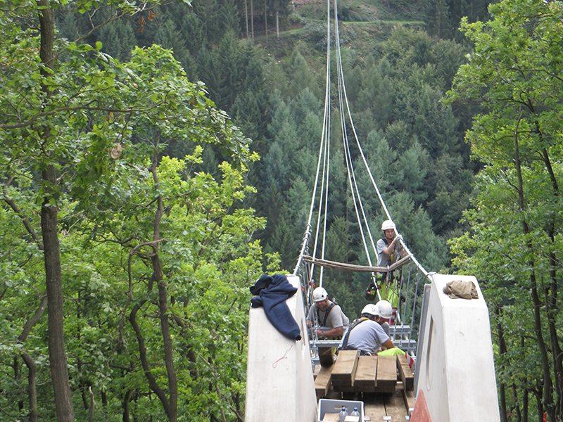 Hier steht ein Foto mit dem Titel: Auf der Mörsdorfer Seite: Ein Brückenkopf, davor der Montagetrupp aus gutgelaunten Schweilzer Spezialisten. Übrigens: der am weitesten vorgeschobene Posten auf dem Seil ist eine Frau (Fotos: Hans-Joachim Schneider)