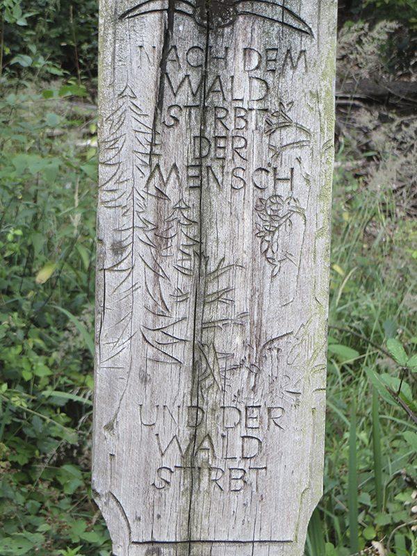 Mahnmal, das an das in den 80er-Jahren so gefürchtete Waldsterben erinnert. Text: Nach dem Wald stirbt der Mensch – und der Wald stirbt
