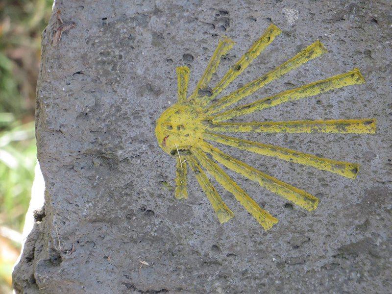 Ein Stein, darauf in Gelb eine stlisierte Muschel: Große Teile des Zuwegs Wilde Endert verlaufen auf der Trasse des Jakobswegs (Foto: Hans-Joachim Schneider)