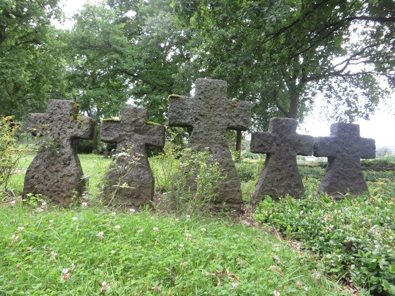 Steinerne Grabkreuze im Grün zugewachsenen Areal des Ehrenfriedhofs