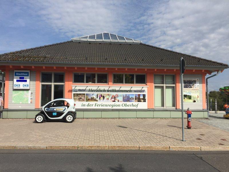 Haus, Gebäude der Touristen-Information von Oberhof, davor parkt ein Auto.