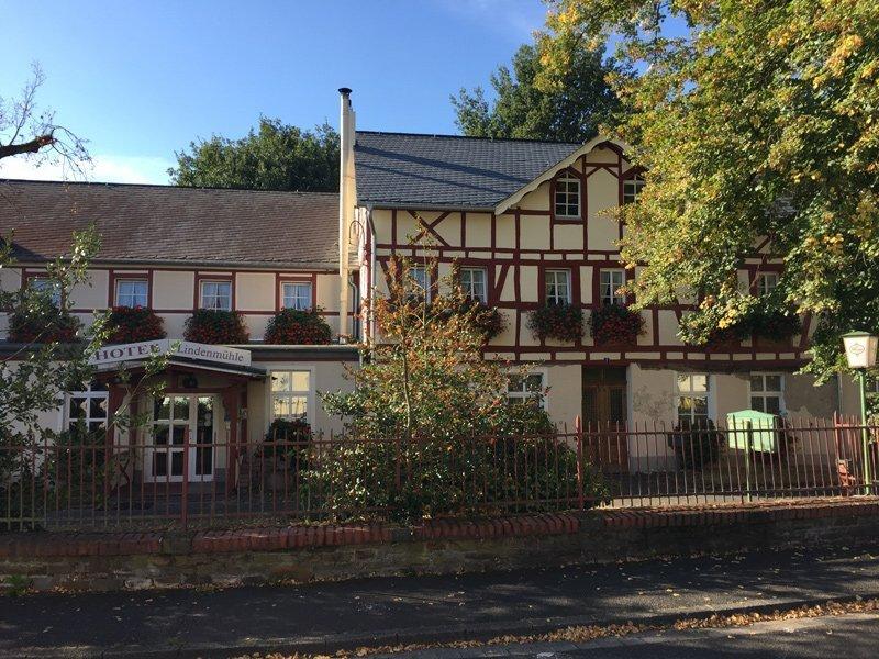 Hotel Lindenmühle, ein vorsichtig renoviertes Fachwerkhaus, darüber strahlt blauer Himmel