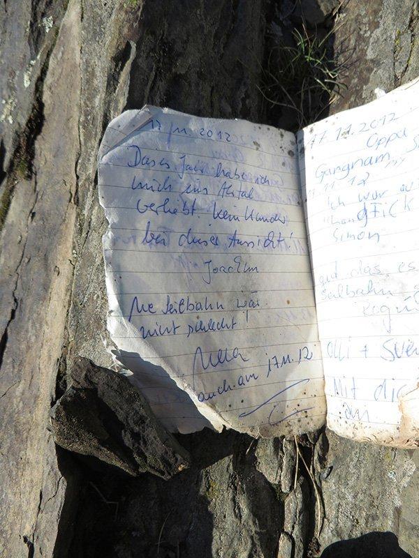 Gipfelbuch: ein altes Heft, weiße Seiten, zerfleddert, mit blauer Tinte beschrieben.