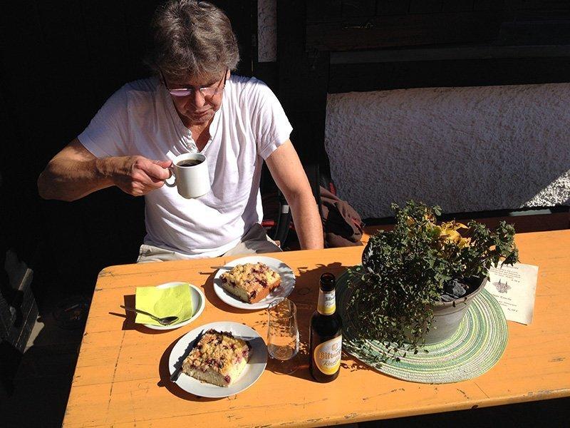 Ein Tisch in Orange, Kuchen, Kaffee und Bier und der Autor bei einer Stärkung