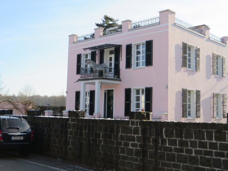 Haus, rosa gestrichen, Auf dem Balkon ein fast lebensgroßes Zebra aus Pappmachèe