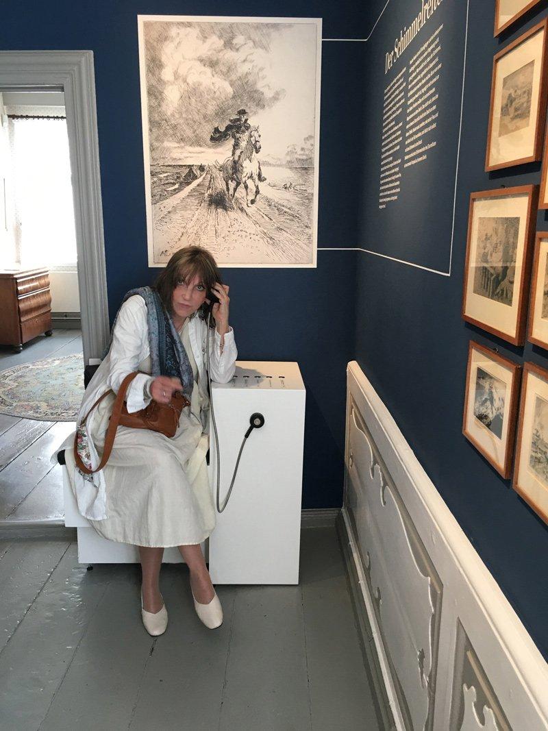 Frau im Schimmelreiter-Zimmer, die sich gelesene Passagen aus dem werk anhört