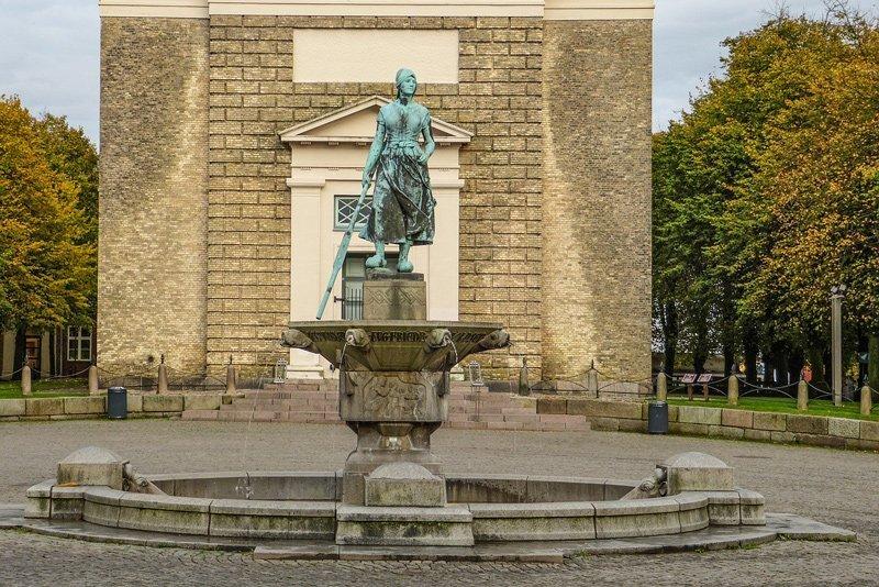 Der Brunnen mit der Tinefigur vor der Marienkirche auf dem Marktplatz in Husum