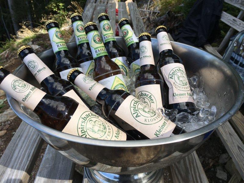 Schüssel mit Bierflaschen auf Eis. Ein erfrischendes Getränk nach einer anstrengenden Wanderung