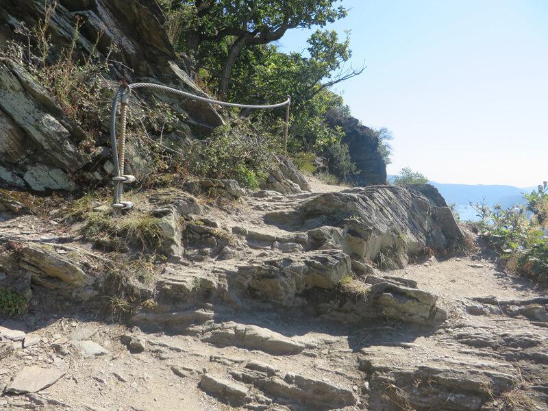 Felsiger Untergrund, eine Seilsicherung für den Wanderer, rechts geht es steil ins Tal hinunter