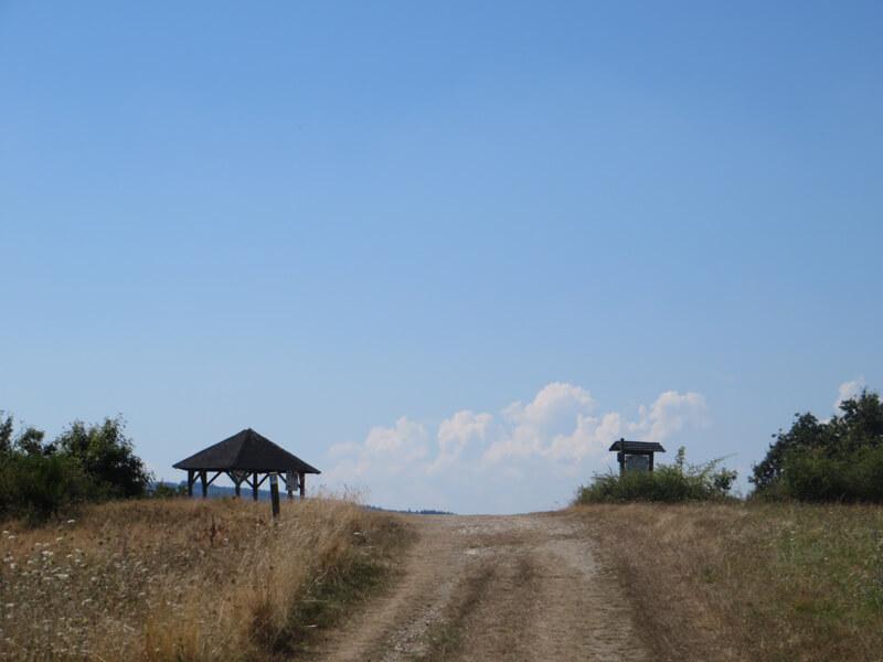 Ein weiße Quellwolke am sommerlichen HImmel. Fast nur als Schattenriss erkennbar: eine Schutzhütte links vom Weg, auf der rechten Seite eine Infotafel.