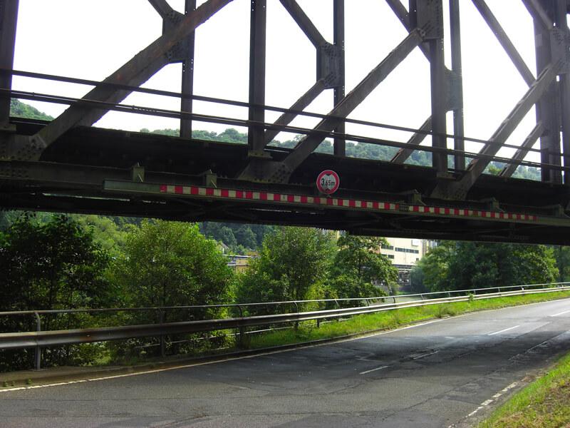 unten eine Straße begrenzt von grünem Gebüsch, darüber die Eisenkonstruktion einer alten Eisenbahnbrücke, die Hohenrheinbrücke bei Niederlahnstein