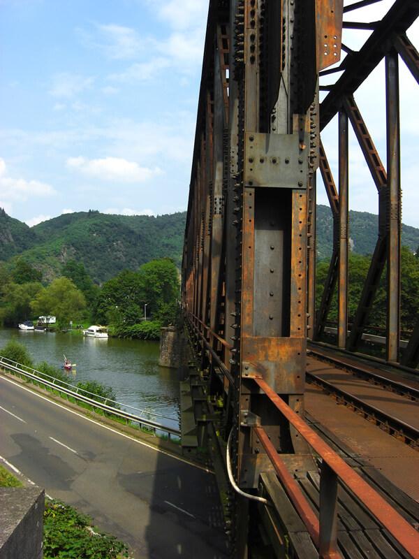 Das rostige Gerüst einer Eisenbahnbruecke, der sogenannten Hohenrheinbrücke, über einen Fluss, im Vordergrund eine Straße, über allem blauer HImmel.