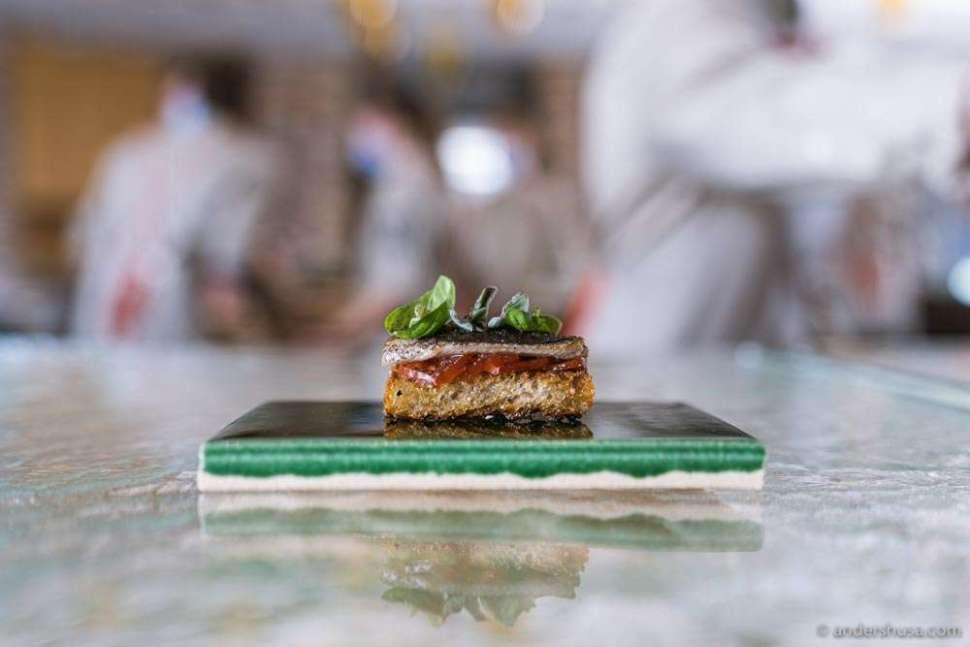 Danish sardine, tomato, and basil on crispy sourdough bread.