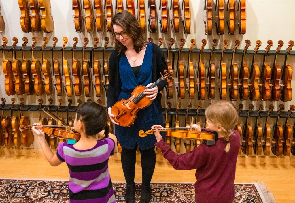 Violin teacher instructs two young students