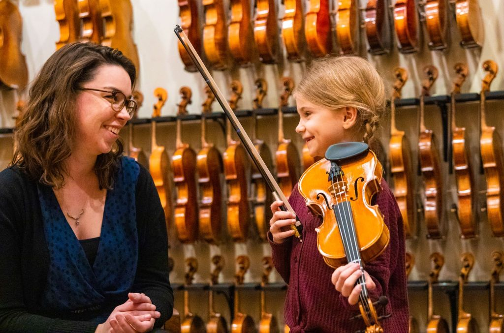 Violin teacher and young student laughing
