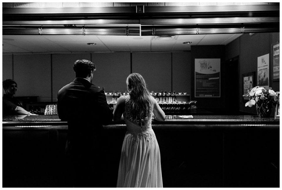 Black and white shot of bride and groom at the bar at PostOak Lodge in Tulsa, OK  Tulsa Wedding Photographer  PostOak Lodge Wedding  Destination Wedding Photographer  Andi Bravo Photography