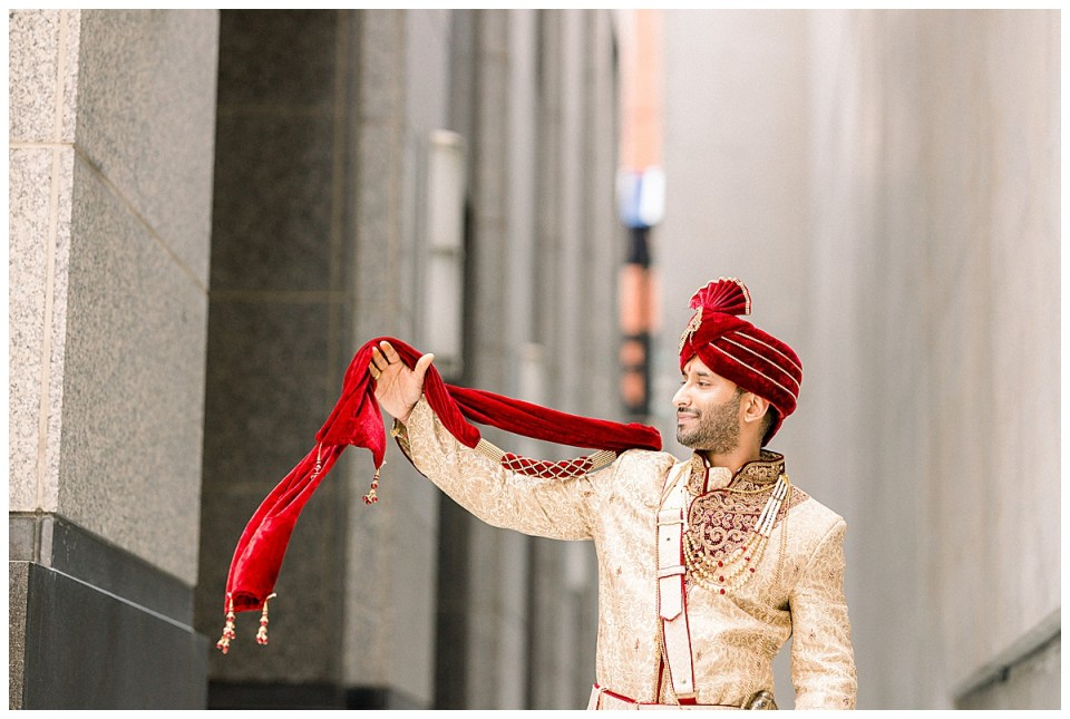 Indian groom holding out crimson wedding ceremonial scarf| Indian wedding Tulsa| Tulsa wedding photographer| Andi Bravo Photography
