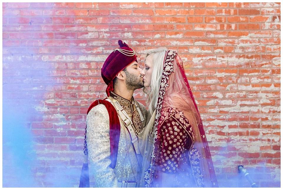 Bride and groom kiss with purple smoke surrounding them| Hindu wedding| Tulsa wedding| Tulsa wedding photographer| Andi Bravo Photography