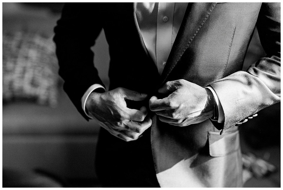 Black and white close up shot of groom buttoning up his suit jacket| The Mayo Hotel| Tulsa weddings| Tulsa wedding photographer| Destination wedding photographer| Andi Bravo Photography