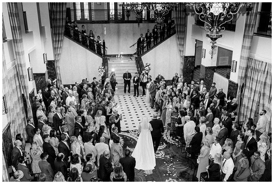 Black and white aerial shot of bride walking down the aisle with her father| The Mayo Hotel Wedding| Tulsa wedding photographer| Destination wedding photographer| Andi Bravo Photography