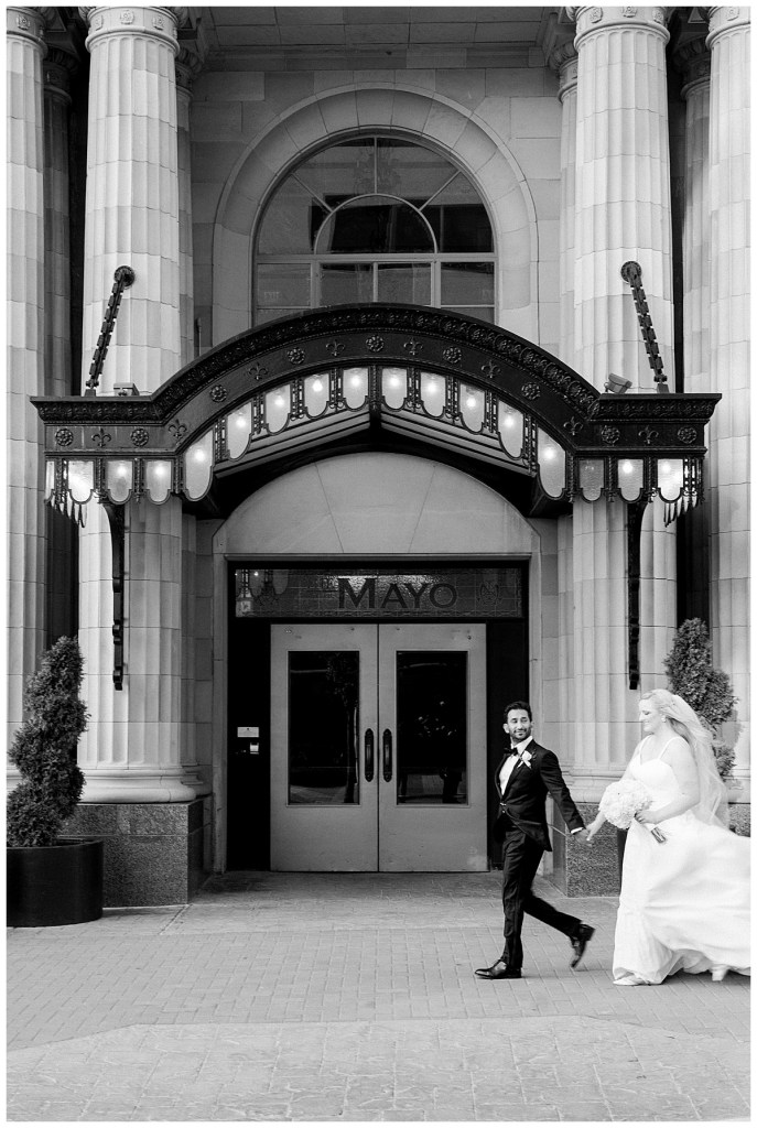 Black and white of bride and groom walking hand in hand in front of The Mayo Hotel| Tulsa weddings| Tulsa wedding photographer| Andi Bravo Photography