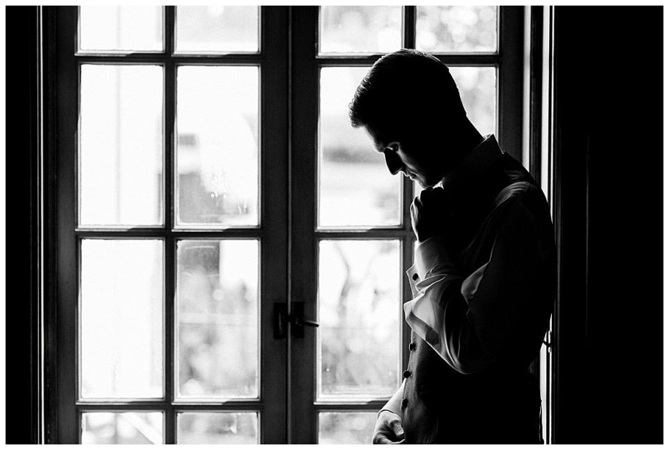 Black and white of groom standing next to window| Tulsa wedding venue| Andi Bravo Photography