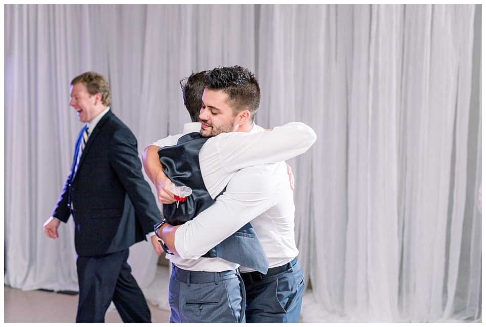 Groom hugs friend who caught garter during garter toss| Andi Bravo Photography