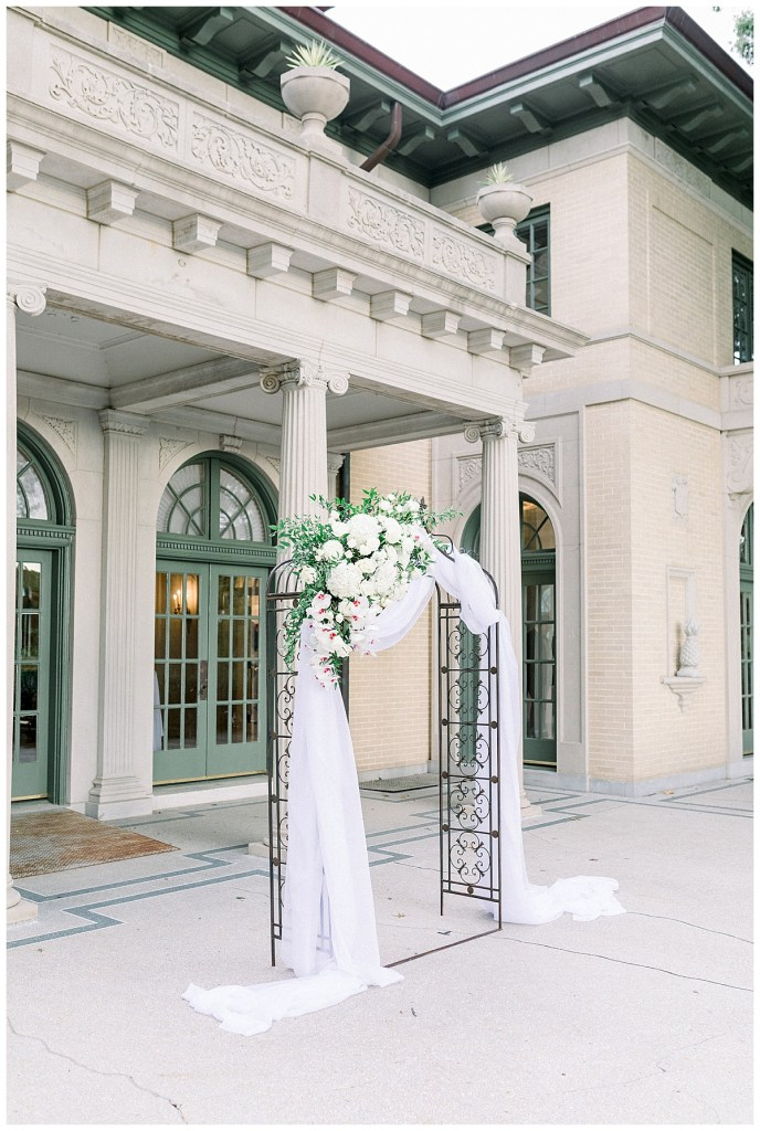 White & green floral wedding arch in front of The Mansion at Woodward Park| Tulsa wedding venue| Andi Bravo Photography