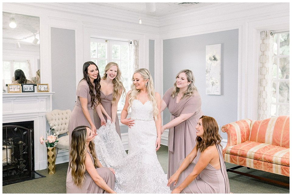 Bridesmaids all holding part of bride's wedding gown and smiling| bride and bridesmaids| Tulsa wedding venue| The Mansion at Woodward Park| Tulsa wedding photographer| Andi Bravo Photography