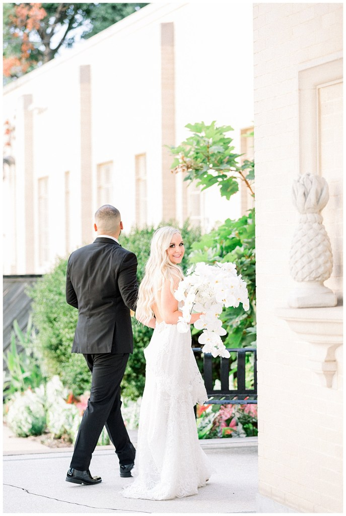Bride looks over shoulder smiling while walking with groom| Tulsa weddings| White orchid bridal bouquet| Andi Bravo Photography