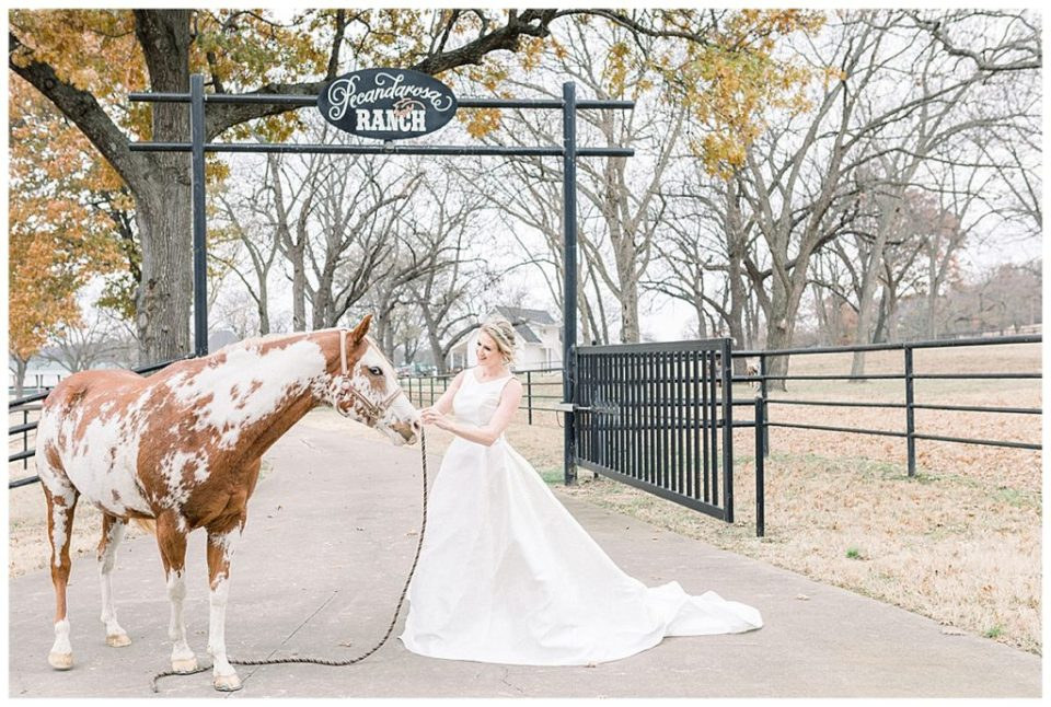 Bride standing with horse in front of Pecandarsa Ranch entrance