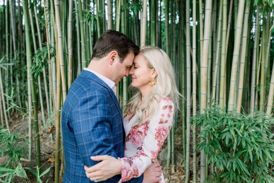 Couple nuzzles in front of large bamboo in Fort Worth Botanical Gardens