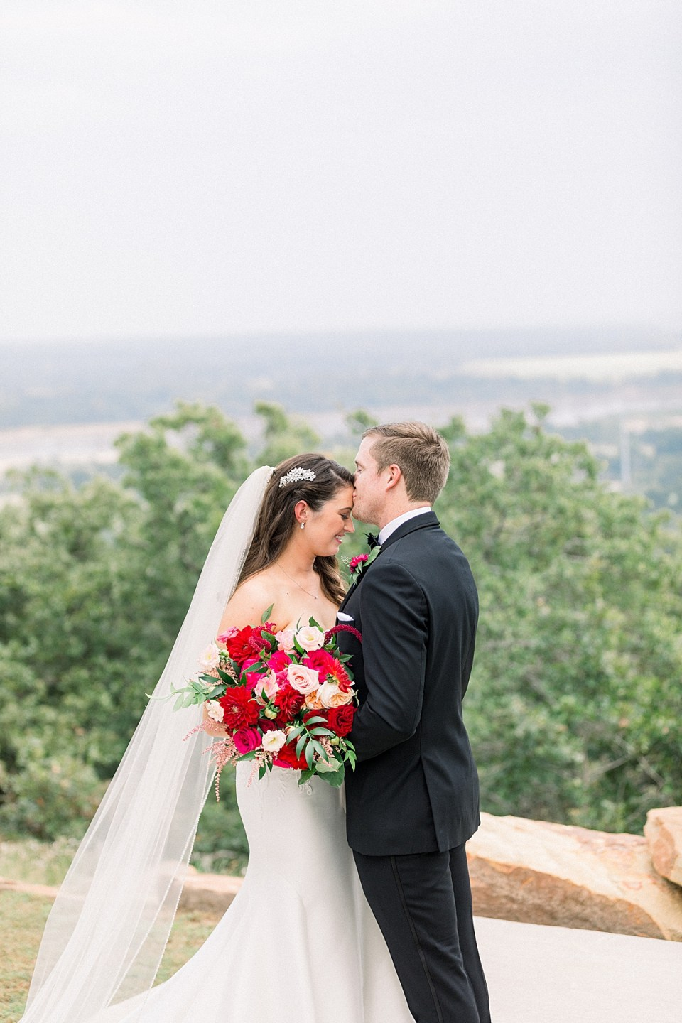 Groom kisses bride on forehead at Dream Point Ranch wedding